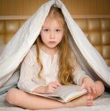 Kleines Mädchen, das auf dem Bett sitzt und ein Buch liest Stockfoto