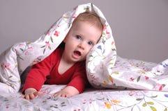 Kleines Mädchen, das auf dem Bett spielt Lizenzfreies Stockfoto
