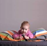 Kleines Mädchen, das auf dem Bett spielt Stockfotos
