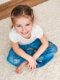 Kleines Mädchen, das auf dem Boden sitzt Lizenzfreie Stockbilder