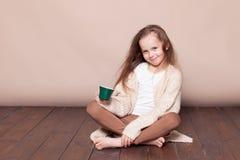 Kleines Mädchen, das auf dem Boden und dem trinkenden Tee sitzt Stockfoto