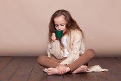 Kleines Mädchen, das auf dem Boden und dem trinkenden Tee sitzt Stockfotografie