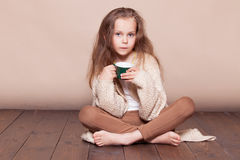 Kleines Mädchen, das auf dem Boden und dem trinkenden Tee sitzt Stockfotos