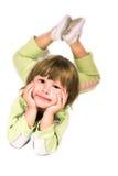Kleines Mädchen, das auf dem Fußboden liegt Stockfotografie
