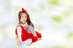 Kleines Mädchen, das auf dem Fußboden sitzt Stockbild