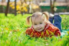Kleines Mädchen, das auf dem Gras im Park liegt Lizenzfreie Stockfotografie