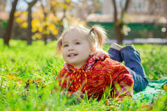 Kleines Mädchen, das auf dem Gras im Park liegt Lizenzfreies Stockfoto