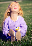 Kleines Mädchen, das auf dem Gras sitzt lizenzfreie stockbilder