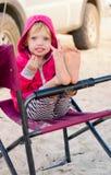 Kleines Mädchen, das auf dem kampierenden Stuhl sitzt Stockfotografie