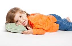 Kleines Mädchen, das auf dem Kissen liegt Stockfotografie