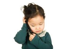 Kleines Mädchen, das auf dem Mobiltelefon spricht Stockbilder