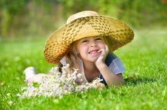 Kleines Mädchen, das auf dem Rasen liegt Lizenzfreie Stockfotos