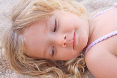 Kleines Mädchen, das auf dem Sand liegt Stockfotografie