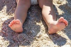 Kleines Mädchen, das auf dem Sand sitzt und mit Plastikspielwaren spielt Lizenzfreies Stockbild