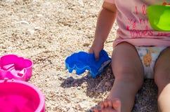 Kleines Mädchen, das auf dem Sand sitzt und mit Plastikspielwaren spielt Lizenzfreie Stockfotos