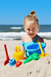 Kleines Mädchen, das auf dem Sandstrand spielt Lizenzfreie Stockfotografie