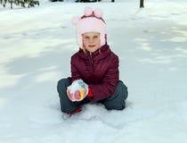 Kleines Mädchen, das auf dem Schnee spielt Lizenzfreies Stockbild