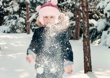 Kleines Mädchen, das auf dem Schnee spielt Stockfoto