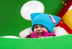 Kleines Mädchen, das auf dem Spielplatz, den Spaß habend spielt, der den Tag des Winters auf der Straße spinnend im Park spielt Lizenzfreies Stockbild
