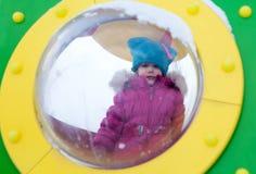 Kleines Mädchen, das auf dem Spielplatz, den Spaß habend spielt, der den Tag des Winters auf der Straße spinnend im Park spielt Stockfotos