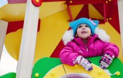 Kleines Mädchen, das auf dem Spielplatz, den Spaß habend spielt, der den Tag des Winters auf der Straße spinnend im Park spielt Stockfotografie