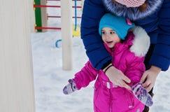 Kleines Mädchen, das auf dem Spielplatz, den Spaß habend spielt, der den Tag des Winters auf der Straße spinnend im Park spielt Lizenzfreies Stockfoto