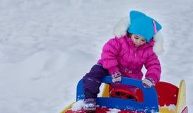 Kleines Mädchen, das auf dem Spielplatz, den Spaß habend spielt, der den Tag des Winters auf der Straße spinnend im Park spielt Lizenzfreie Stockbilder