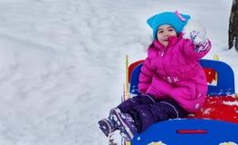 Kleines Mädchen, das auf dem Spielplatz, den Spaß habend spielt, der den Tag des Winters auf der Straße spinnend im Park spielt Lizenzfreie Stockfotografie