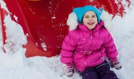 Kleines Mädchen, das auf dem Spielplatz, den Spaß habend spielt, der den Tag des Winters auf der Straße spinnend im Park spielt Stockfoto