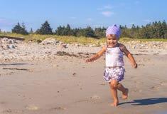 Kleines Mädchen, das auf dem Strand läuft Stockbild
