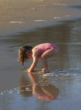 Kleines Mädchen, das auf dem Strand mit ihrer Reflexion auf dem Wasser spielt Lizenzfreies Stockfoto