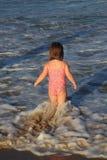 Kleines Mädchen, das auf dem Strand spielt  Stockfoto