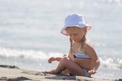 Kleines Mädchen, das auf dem Strand sitzt Lizenzfreies Stockbild