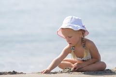 Kleines Mädchen, das auf dem Strand sitzt Stockbild
