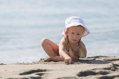 Kleines Mädchen, das auf dem Strand sitzt Lizenzfreie Stockfotos