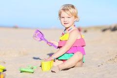Kleines Mädchen, das auf dem Strand spielt Lizenzfreie Stockfotografie