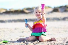 Kleines Mädchen, das auf dem Strand spielt Lizenzfreie Stockfotos