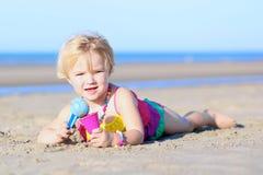 Kleines Mädchen, das auf dem Strand spielt Stockfotografie