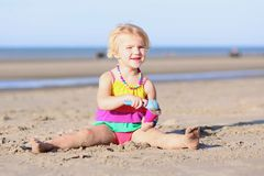 Kleines Mädchen, das auf dem Strand spielt Lizenzfreies Stockbild