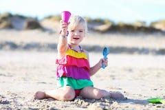 Kleines Mädchen, das auf dem Strand spielt Stockfotos