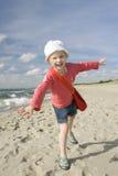 Kleines Mädchen, das auf dem Strand spielt Stockbild