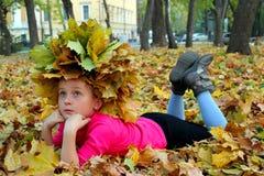 Kleines Mädchen, das auf den gelben Blättern liegt Lizenzfreie Stockbilder