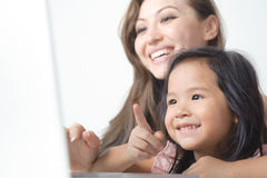 Kleines Mädchen, das auf den Laptop glücklich zeigt Stockfotos