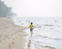 Kleines Mädchen, das auf den Strand läuft stockbild