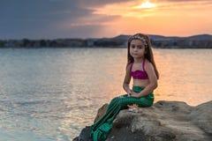 Kleines Mädchen, das auf der Klippe sitzt Lizenzfreie Stockfotografie