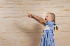 Kleines Mädchen, das auf der linken Seite des Rahmens zeigt Stockfotografie