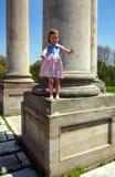 Kleines Mädchen, das auf der Spalte steht Stockfoto