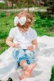 Kleines Mädchen, das auf der Tablette spielt Mädchen, das eine Tablette verwendet Lizenzfreie Stockbilder