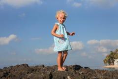Kleines Mädchen, das auf die felsige Küste geht Lizenzfreie Stockbilder