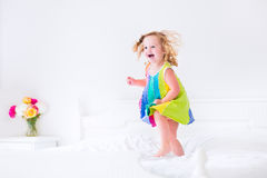 Kleines Mädchen, das auf ein Bett springt Lizenzfreie Stockfotos